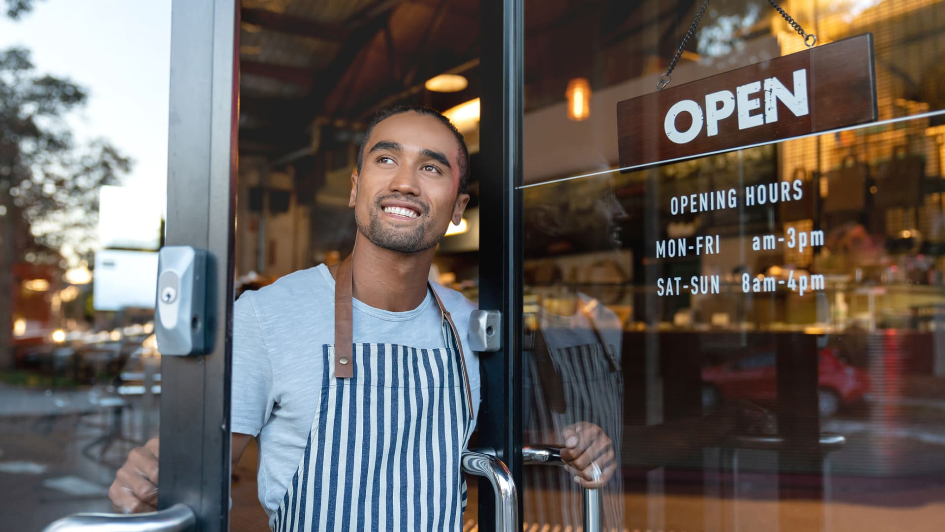 A business owner opens the door of his shop
